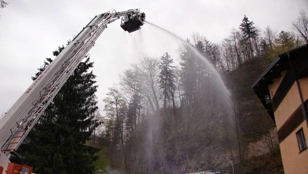 Drei Feuerwehrmänner löschten hoch oben von der Drehleiter aus. (Bild: FF Golling)