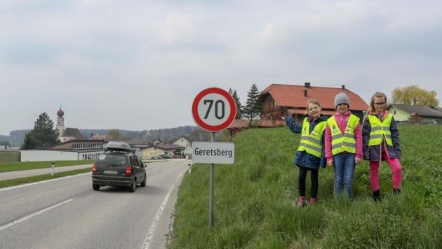 Sarah, Rebecca und Irina neben der Straße, die die Kinder überqueren müssen. (Bild: Scharinger Daniel)