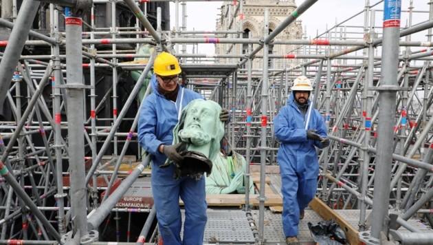 Arbeiter schaffen während der Renovierungsarbeiten von Notre Dame im März einen Teil einer Statue vom Dach der Kathedrale. (Bild: AFP )