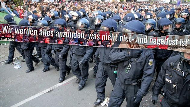 """""""Wir werden alles anzünden, was nicht niet- und nagelfest ist"""", sagt eine Vertreterin der Gruppe """"Radikale Linke Berlin"""" in einem Interview. (Bild: AFP, Lower Class Magazine, krone.at-Grafik)"""