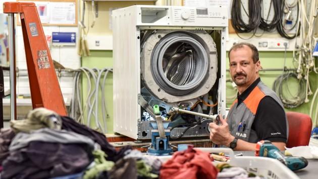 Christian Pöchhuber kontrolliert den Reparatur-Fortschritt bei einer Waschmaschine. (Bild: Markus Wenzel)