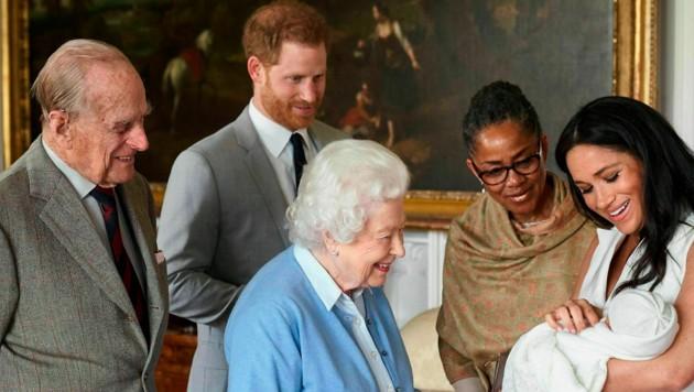Prinz Harry und Herzogin Meghan zeigen den stolzen (Ur-)Großeltern - neben Queen Elisabeth II. und Prinz Philip ist auch Meghans Mutter Doria Ragland dabei - den kleinen Archie. (Bild: AP)