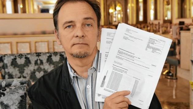 Robert F. mit seinem Einkommensteuerbescheid für ein Einkommen, das er nie erhalten hat (Bild: Klemens Groh)