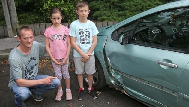Sandor D. mit Tochter Julia (8) und Sohn Julian (11) neben dem demolierten Auto (Bild: Peter Tomschi )
