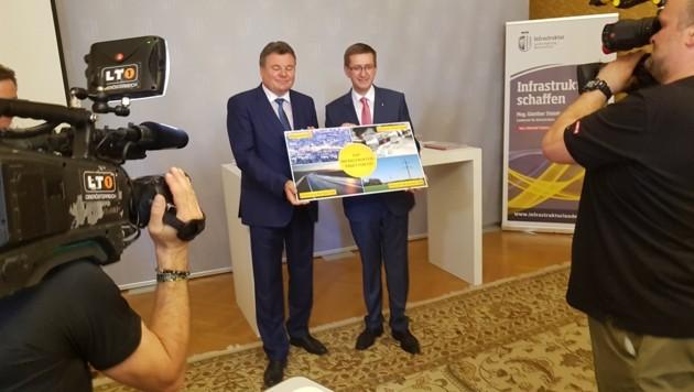 Die Landesräte Günther Steinkellner (links) und Markus Achleitner (rechts) präsentieren symbolisch ihr gemeinsames Zukunftspaket für Infrastruktur. (Bild: Werner Pöchinger)