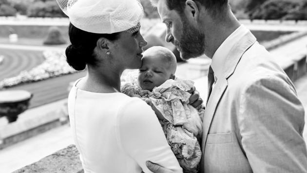 Harry und Meghan wenden sich im Garten von Schloss Windsor einander liebevoll zu. Meghan hält den in seinem voluminösen Taufkleid selig schlummernden Archie im Arm. (Bild: AFP)