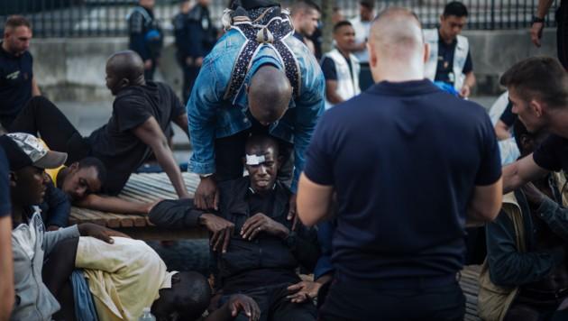 Bei kleineren Zusammenstößen mit der Polizei leicht verletzte Migranten werden medizinisch versorgt. (Bild: AP)