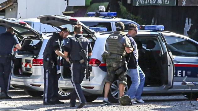 Ein Cobra-Beamter führt einen der beiden Täter ins Polizeiauto. (Bild: Tschepp Markus)