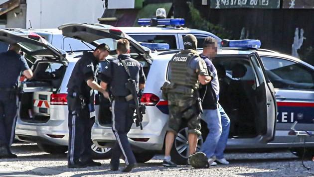 Ein Cobra-Beamter führt einen der beiden Verdächtigen zum Polizeiauto. (Bild: Markus Tschepp)