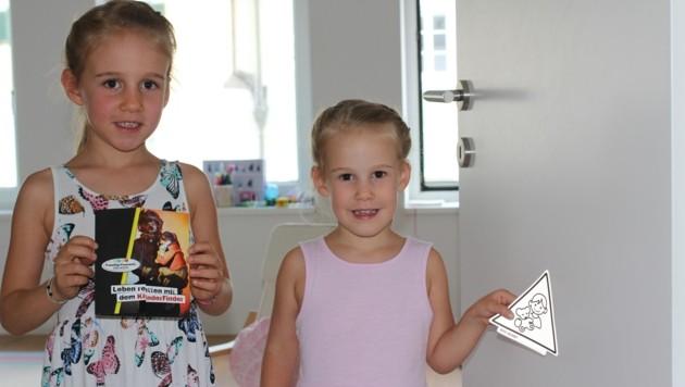 """Clara und Catharina (r.) haben ihre Kinderzimmertüre bereits mit dem """"KinderFinder"""" versehen. (Bild: FF Gmunden)"""