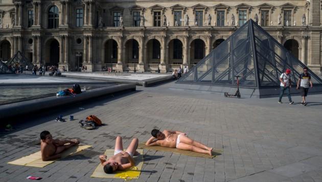 Diese Männer legen direkt neben dem Louvre in Paris einen erfrischenden Badestopp ein. (Bild: AP)