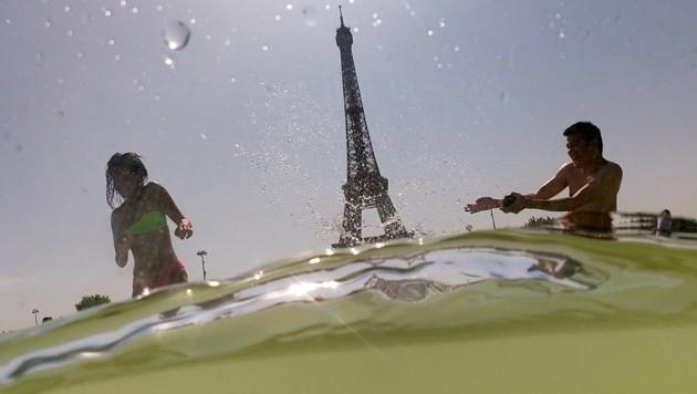Die Paris suchten am Donnerstag die Abkühlung in der Nähe des Eiffelturms. (Bild: AFP)