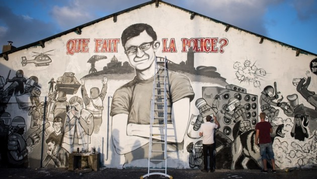 Graffiti-Künstler bemalen die Wände mit einem Bild von Steve Canico und Szenen aus der Todesnacht. (Bild: AFP)