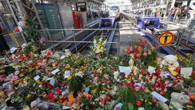 Ein Meer aus Blumen, Kuscheltieren und Beileidsbekundungen am Bahnsteig 7 (Bild: APA/dpa/Arne Dedert)