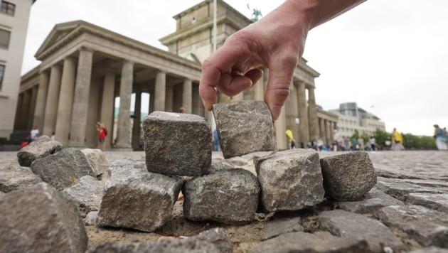 Symbolakt: Aus Pflasterscheinen wird eine kleine Mauer vor dem Brandenburger Tor errichtet. (Bild: APA/dpa/Jörg Carstensen)