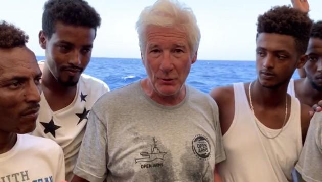 Aufnahme aus dem Jahr 2019: Richard Gere im Gespräch mit den geretteten Migranten auf der Open Arms (Bild: AFP)