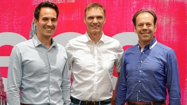 NEOS-Wien-Klubobmann Christoph Wiederkehr (li.) und der pinke Penzinger Klubobmann Wolfgang Gerold (re.) freuen sich über den grünen Neuzugang Roland Kariger (Mitte). (Bild: NEOS Wien)