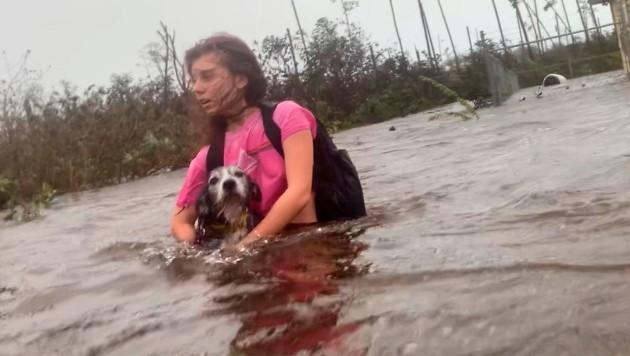 Ein junges Mädchen wird aus den Fluten in Sicherheit gebracht, auf dem Arm trägt sie ihren Hund. (Bild: AP)