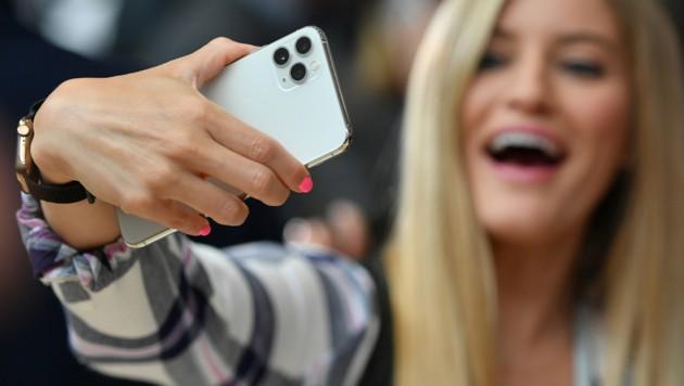 Eine Influencerin macht für ihre Gefolgschaft ein Selfie mit Apples iPhone 11 Pro. (Bild: APA/AFP/Josh Edelson)