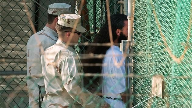US-Soldaten mit einem Guantanamo-Häftling (Bild: AFP)