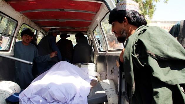 Eine bei der Attacke in der Provinz Helmand getötete Frau wird abtransportiert. (Bild: AP)