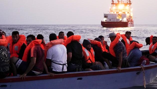 Eine alltägliche Szene im Mittelmeer: Migranten warten in einem völlig überfüllten Boot auf ihre Rettung. (Bild: AP)