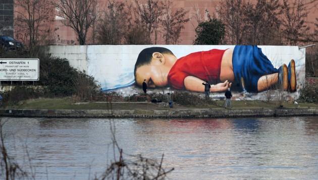 Ein Graffito von Justus Becker und Oguz Sen zeigt den ertrunkenen syrischen Flüchtlingsbuben Alan Kurdi in Frankfurt am Main. (Bild: AFP)