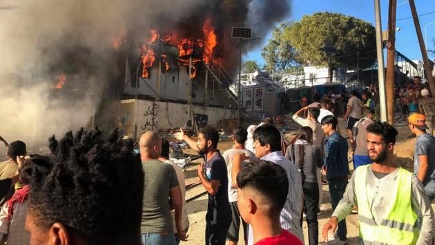 Lesbos: Flüchtlinge stehen neben brennenden Hauscontainern (Bild: AP)
