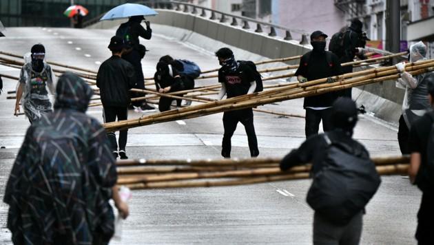 Demonstranten bei der Errichtung von Straßenblockaden (Bild: APA/AFP/Anthony WALLACE)