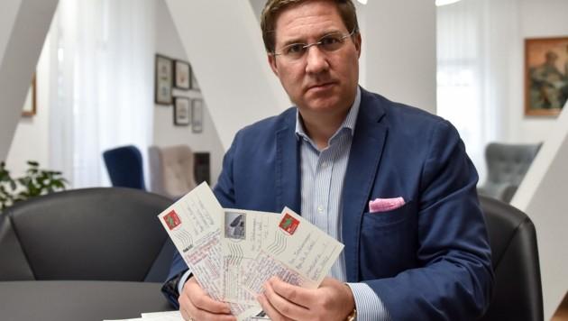 Der Welser FP-Stadtchef Andreas Rabl mit den Postkarten (Bild: Wenzel Markus)