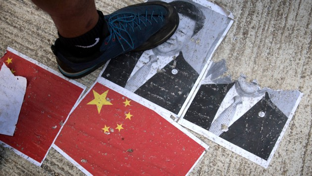 Demonstranten in Hongkong zertrampeln ein Bild des chinesischen Staatschefs Xi Jinping. (Bild: AFP)