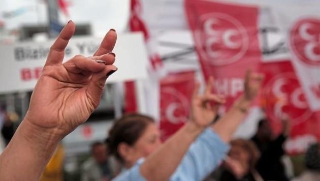 """Der """"Wolfsgruß"""" ist das Merkmal und Erkennungszeichen der """"Grauen Wölfe"""". Er stellt einen Wolfskopf dar. Der Gründer der Bewegung, Alparslan Türkes, meinte dazu: """"Der kleine Finger symbolisiert die Türken, der Zeigefinger den Islam, der Kreis die Welt. Der Punkt, an dem sich die drei Finger treffen, ist der Stempel, mit dem wir der Welt den türkischen Islam aufdrücken."""" (Bild: AP)"""