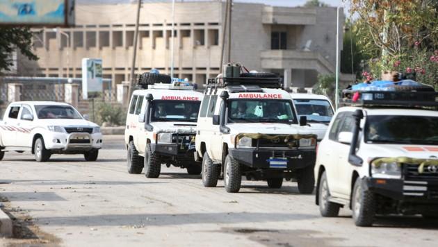 Die abziehenden Kämpfer werden von Rettungsfahrzeugen begleitet. (Bild: APA/AFP/Nazeer Al-khatib)