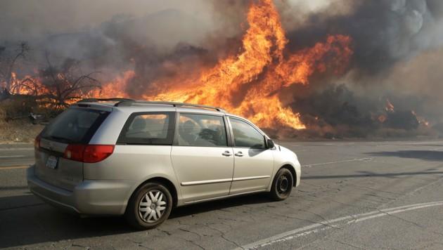 Autofahrer versuchen am Sierra Highway den nahen Flammen zu entkommen. (Bild: AP)