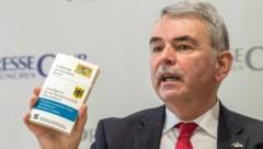 Das Justizopfer Gustl Mollath hält während einer Pressekonferenz im Presseclub München ein Exemplar der Bayerischen Verfassung und des Deutschen Grundgesetzes hoch. (Bild: APA/dpa/Lino Mirgeler)