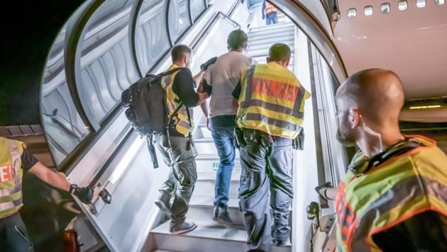 Polizeibeamte begleiten einen Afghanen auf dem Flughafen Leipzig-Halle in ein Charterflugzeug. (Archivbild) (Bild: APA/dpa/Michael Kappeler)