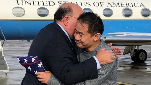 Umarmung zwischen US-Botschafter Edward T. McMullen und dem freigelassenen US-Bürger Xiyue Wang auf dem Flughafen von Bern (Bild: APA/AFP/US State Department/HO)