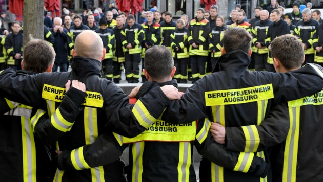 Kameraden des totgeschlagenen Feuerwehrmanns trafen sich, um am Tatort öffentlich zu trauern. (Bild: APA/dpa/Stefan Puchner)