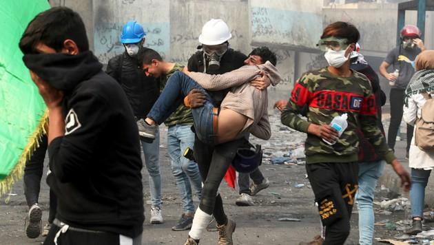 Ein Regierungsgegner bringt bei Auseinandersetzungen mit den Sicherheitskräften in Bagdad einen verletzten Kollegen in Sicherheit. (Bild: AP)