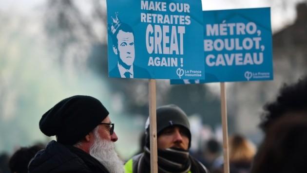 """Ein nicht ganz ernst gemeinter Slogan, der Präsident Macron auffordert, die Pensionen der Franzosen in Anlehnung an den Wahlkampfspruch von US-Präsident Donald Trump """"wieder großartig zu machen"""". (Bild: APA/AFP/Christophe ARCHAMBAULT)"""