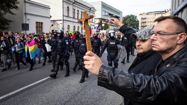 Mit Kreuz und Rosenkranz wappnen sich zwei Polen gegen eine Schwulenparade in der Stadt Lublin im Osten des Landes. (Bild: AFP)