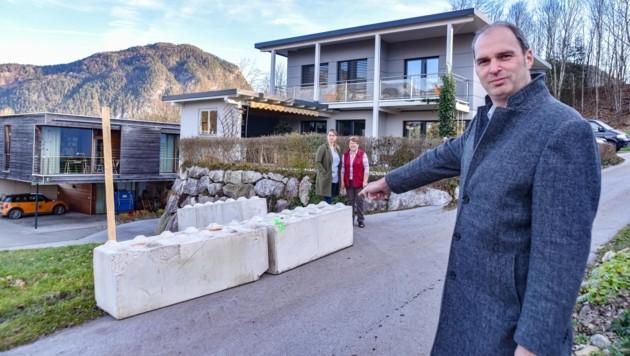 """Der unmittelbare Anrainer Richard Holzner zeigt auf die massiven Betonblöcke und stellt die berechtigte Frage: """"Wie soll auf dieser schmalen Gemeindestraße der Schneepflug noch seiner Arbeit nachkommen?"""" (Bild: Hubert Berger)"""