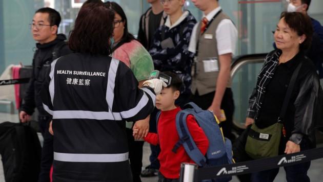 Medizinisches Personal überprüft die Körpertemperatur von in Hongkong ankommenden Flugpassagieren. (Bild: AP)