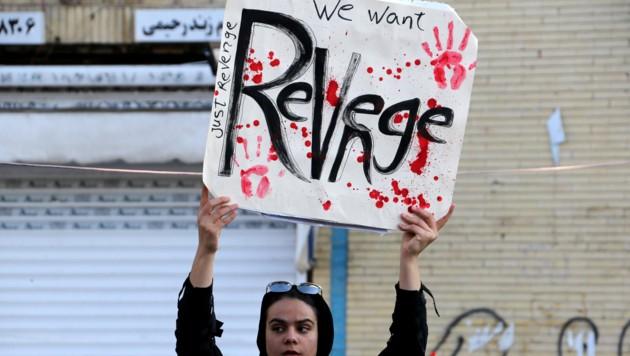 Eine Frau fordert auf einem Plakat Rache. (Bild: AFP)