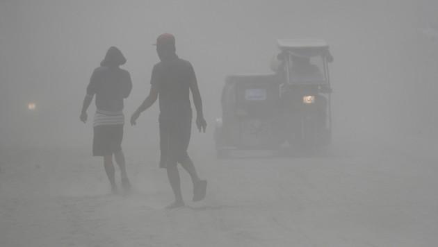 Die Straßen sind verhüllt von Asche und Staub. (Bild: AP)
