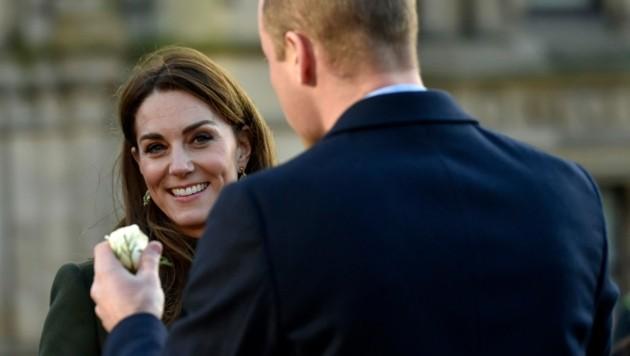 Prinz William hält der lächelnden Herzogin Kate eine weiße Rose hin. (Bild: APA/AP)