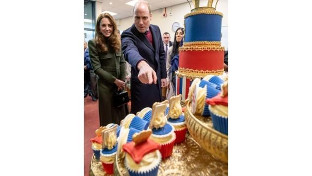 Herzogin Kate und Prinz William staunen über eine Cupcake-Gallerie mit ihren Familienfotos. (Bild: CHARLOTTE GRAHAM / AFP / picturedesk.com)
