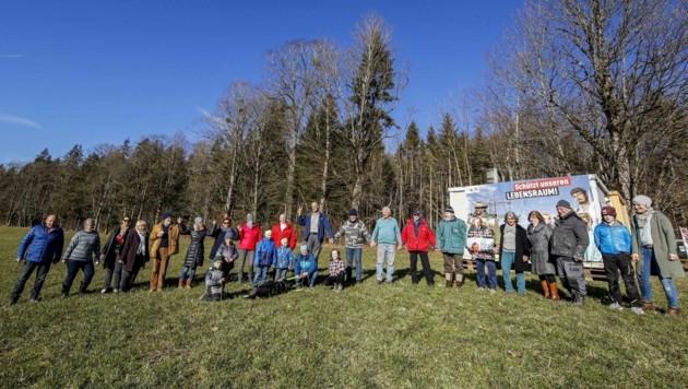 Sie stehen dem Großkonzern mutig entgegen: Die 380-kV-Freileitungsgegner formieren eine Menschenkette als Symbol des Widerstands. Ihren Wachposten in einem Waldstück in Bad Vigaun haben sie in einen Container verlagert. (Bild: Tschepp Markus)