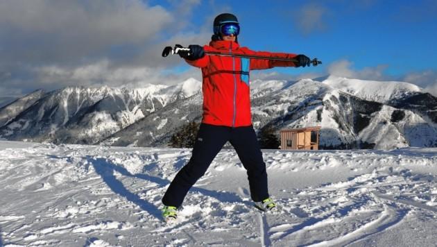 Übung 4: In die Grätsche gehen und abwechselnd Gewicht von einem Bein auf das andere verlagern. Stöcke vor dem Körper halten. (Bild: Philipp Bör)