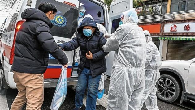Sanitäter in Schutzanzügen bringen einen möglicherweise mit dem Coronavirus Infizierten in ein Spital in Wuhan. (Bild: AFP)